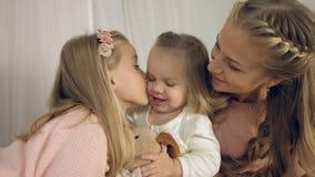 亲吻小女儿和他们的玩具的母亲 图库摄影
