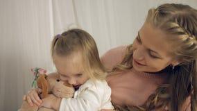 亲吻小女儿和他们的玩具的母亲 免版税库存图片