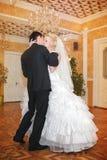 亲吻并且跳舞年轻新娘和新郎在设宴大厅 免版税库存图片