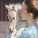 亲吻微型驹的年轻逗人喜爱的妇女 关闭照片 图库摄影