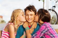 亲吻微笑的两个美丽的女孩一个逗人喜爱的男孩 免版税库存照片