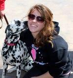 亲吻微笑的青少年的女孩的母Dalmation狗 免版税图库摄影