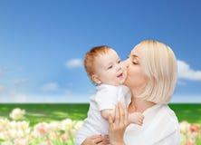 亲吻微笑的婴孩的愉快的母亲 库存照片