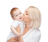亲吻微笑的婴孩的愉快的母亲 免版税图库摄影