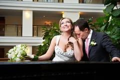 亲吻愉快的新娘和新郎在旅馆内部  免版税库存图片
