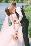 亲吻愉快的新娘的新郎在池塘附近 免版税库存照片