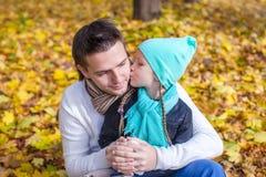 亲吻愉快的父亲的小女孩在秋天公园 图库摄影