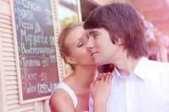 亲吻户外在欧洲城市布局的夫妇 餐馆菜单的背景 免版税库存照片