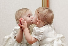亲吻镜子的婴孩 库存图片