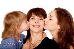 亲吻母亲的二个女儿。 母性概念。 免版税库存照片