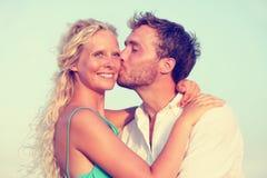 亲吻浪漫的夫妇享受日落在海滩 免版税库存照片