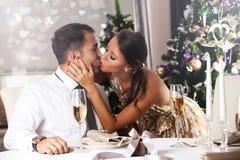 亲吻浪漫的夫妇,在家庆祝圣诞节 库存图片