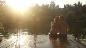 亲吻浪漫的夫妇,当坐由河在日落时 股票视频
