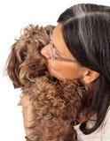 亲吻狗伴侣的妇女 免版税库存图片