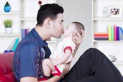 亲吻男婴的英俊的父亲 免版税库存图片