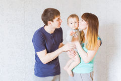 亲吻男婴的年轻愉快的父母 免版税图库摄影