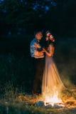 亲吻的一对美好的年轻夫妇的画象在火附近夜 库存照片