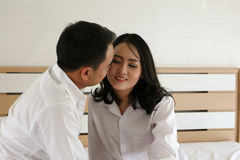 亲吻他的在床上的微笑的亚裔新郎新娘 免版税库存图片