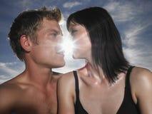 亲吻的夫妇与后边太阳 免版税图库摄影