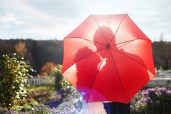 亲吻的夫妇剪影在伞下 免版税库存图片