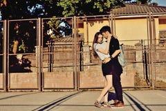 亲吻年轻的夫妇拥抱和室外 免版税库存照片