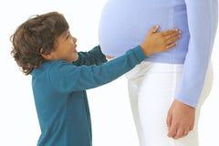 亲吻他的妈妈怀孕的腹部的小男孩 库存图片