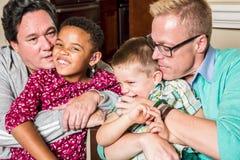 亲吻他们的孩子的父母 免版税库存图片