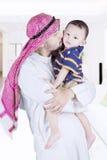亲吻他的孩子的阿拉伯人 免版税库存图片