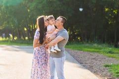 亲吻他们的小女儿的父母室外在夏天 免版税库存照片