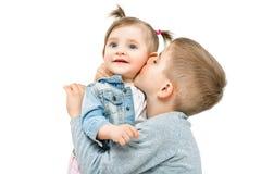 亲吻他的小逗人喜爱的姐妹的兄弟 库存照片