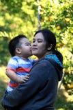 亲吻他的母亲的年轻男孩 图库摄影