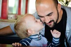 亲吻他的爸爸的小男孩 库存图片