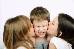 亲吻轻的背景的两个女孩小恼怒的男孩 免版税库存图片