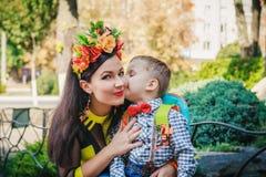 亲吻他的面颊的小男孩母亲 图库摄影