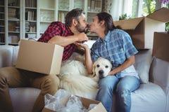 亲吻的年轻夫妇,当打开纸盒箱子时 库存图片