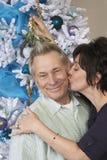 亲吻老人的妇女在槲寄生下 免版税库存照片
