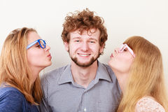 亲吻英俊的人的两名俏丽的妇女 图库摄影