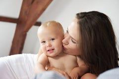 亲吻逗人喜爱的婴孩的一个愉快的母亲的画象 免版税图库摄影