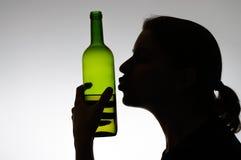 亲吻酒瓶的醺酒的妇女 免版税库存图片