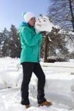 亲吻雪人头的微笑的少妇 免版税图库摄影