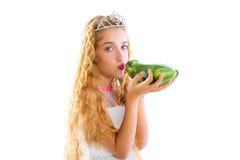 亲吻青蛙绿色蟾蜍的白肤金发的公主女孩 免版税库存图片