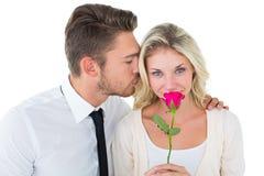 亲吻面颊的英俊的人女朋友拿着玫瑰 免版税库存图片