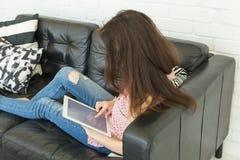 人、内部和休闲概念-有放置在沙发的片剂个人计算机的愉快的少妇 免版税库存图片