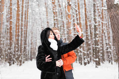 人、季节、爱、技术和休闲概念-拍与智能手机的愉快的夫妇照片在冬天 库存图片