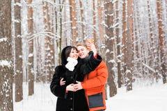 人、季节、爱、技术和休闲概念-拍与智能手机的愉快的夫妇照片在冬天 库存照片