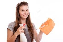 人、家事和家务概念-在家清洗窗口的手套的愉快的妇女与旧布和清洁剂浪花 免版税库存图片