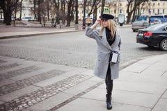 年轻人、熟悉内情和有吸引力的白肤金发的身分在行人交叉路,女孩一个时髦的帽子的和一件灰色外套 免版税库存图片
