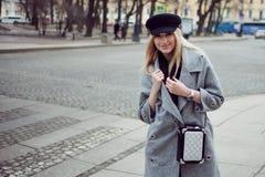 年轻人、熟悉内情和有吸引力的白肤金发的身分在行人交叉路,女孩一个时髦的帽子的和一件灰色外套 免版税库存照片