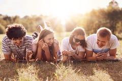 人、生活方式、休闲和休息概念 四个快乐的朋友在地面说谎,有愉快的表示,讲滑稽的传记 免版税库存图片