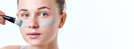 人、秀丽、温泉、整容术和skincare概念 应用面部面具的年轻少年女孩使用刷子 免版税库存图片